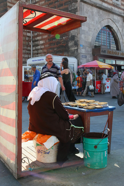 Eminönü. Woman selling birdseeds to tourists for feeding the pigions. <br /> The pigeons 'recycle' it, and say 'thanks' by shitting it back on our heads...