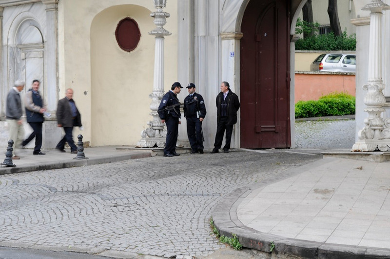 Guards at gate with machine guns at unknown building.