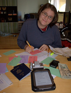 Faye, finishing location notecards with a table of trip stuff.