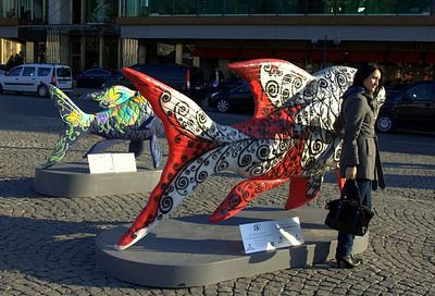Fish sculptures, with a woman posing for a photo. Love the black/red/white color scheme.
