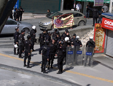 Police, assembled, with riot shields and gas masks.