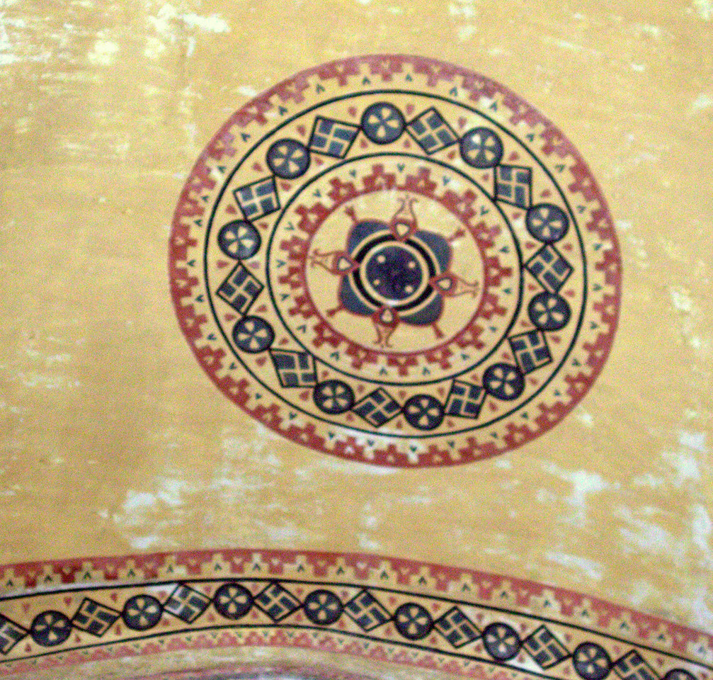 Medallion on ceiling arch with ancient swastika symbols.