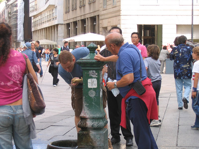 Bryan drinking from a fountain in Milan.
