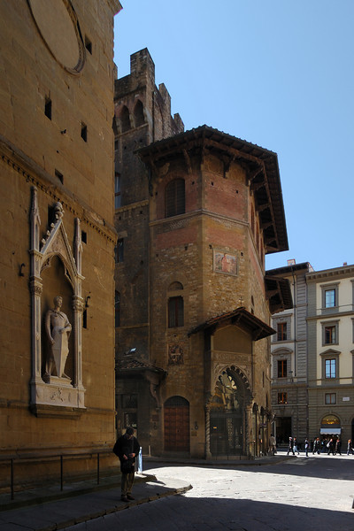 In the front left is Orsanmichele with a statue of St. George by Donatello.  In the middle is the guildhall of the wool merchants, the Palazzo dell' Arte della Lana (1308 A.D.) with an attached fortifiable tower-house.