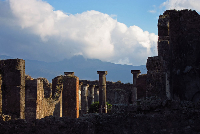 The ruins of Pompeii with Mt. Vesuvius shrouded in clouds.