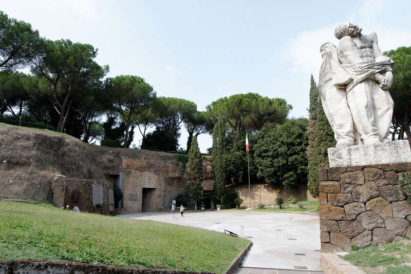 Rome - Ardeatine Memorial.  This is the exterior of the WW-II Ardeatine Memorial.  The entrance to the caves is at the lower centre of the photo, near the two pedestrians.  The large Tomb area is to the left, but can't be seen in this photo.