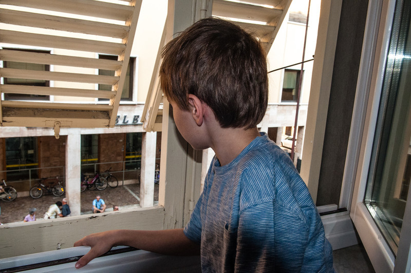 Holden watches a parade from our apartment