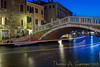 Night scene in Venice. A boat's running lights can be seen as it passes through the canal.
