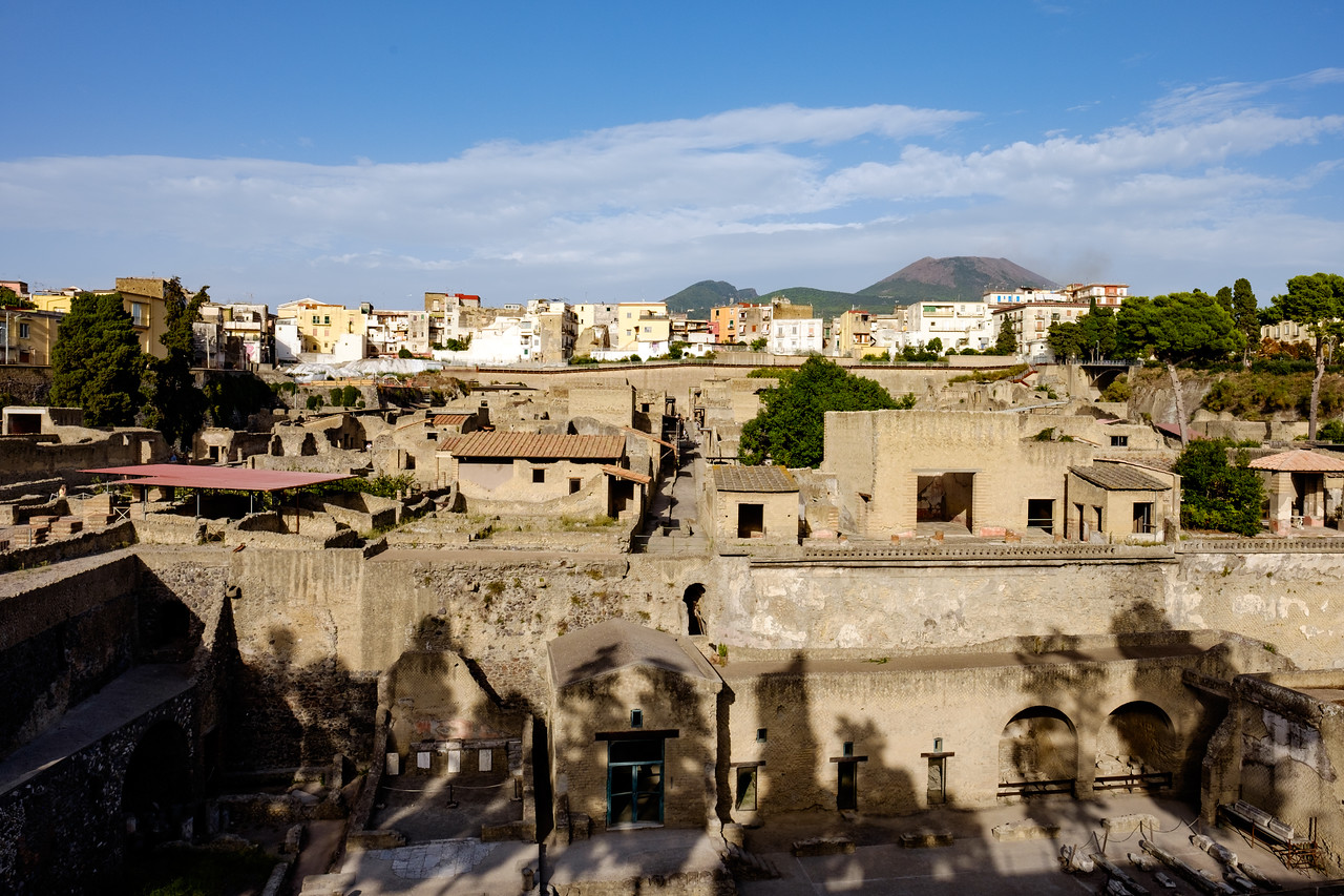 Ancient city with modern city and Vesuvius above it.