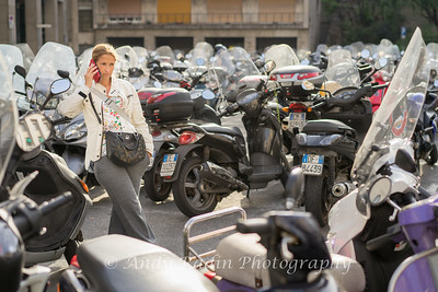 Woman on mobile in a sea of scooters.  Genoa, Italy