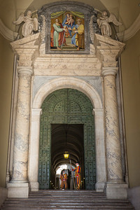 A pair of Pontifical Swiss Guards stand guard at a side door of St. Peter's Basilica.