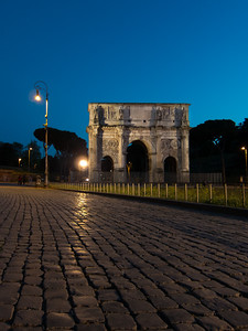The Arch of Constantine and cobblestones at night.