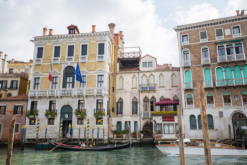 A gondola tour in front of beautiful Grand Canal buildings.