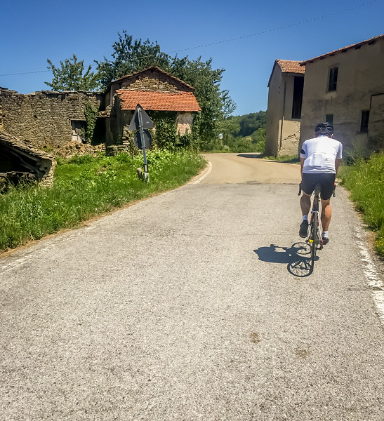 Allan riding past some near ruins on a day in Alta Langhe