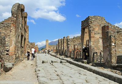 Pompeii - Street (Via Stabiana) and remains of shops, with Mt Vesuvius in the background.