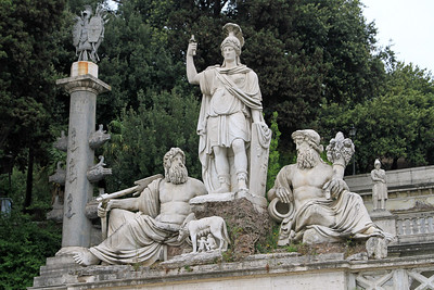 Roman statues in Piazza del Popolo - Dea Roma (Rome) armed with lance and helmet, between the Tiber and the Aniene,and in front is the she-wolf feeding Romulus and Remus.