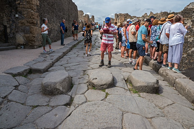 A paved street. Pedestrians used the blocks in the road to cross the street without having to step onto the road, which doubled up as Pompeii's drainage and sewage disposal system. The spaces between the blocks let carriages and wagons  pass along the road