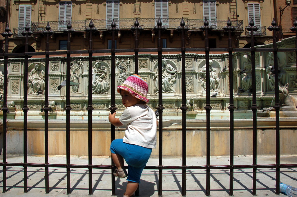 Toddler trying to climb into the Fonte Gaia