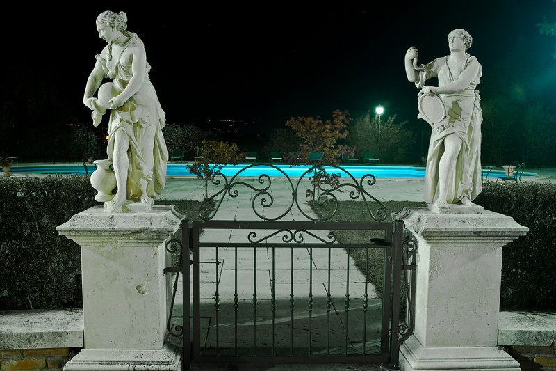 Night view of the pool behind the hotel with the statues by the gate.