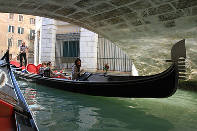 Passing gondolas under a bridge.