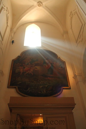 The sun's rays passing through a window into a church.
