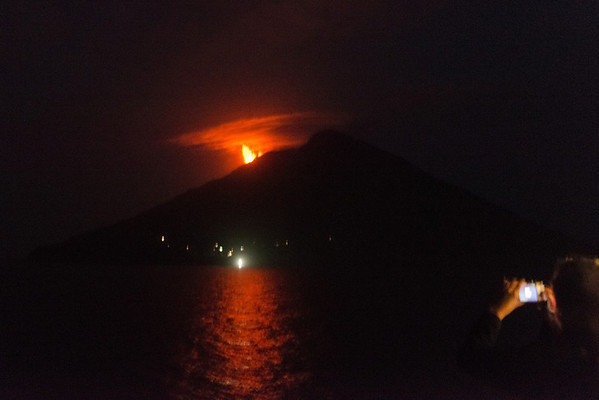 Eruption of the volcano on the island of Stromboli. Photo is noisy because it was taken at ISO 6400, and the ship's motion meant made it impossible to get a sharp photo. From Wikipedia: Stromboli is a small island in the Tyrrhenian Sea, off the north coast of Sicily, containing one of the three active volcanoes in Italy. It is one of the eight Aeolian Islands, a volcanic arc north of Sicily. ... Mt. Stromboli has been in almost continuous eruption for the past 2,000 years. A pattern of eruption is maintained in which explosions occur at the summit craters with mild to moderate eruptions of incandescent volcanic bombs at intervals ranging from minutes to hours. This Strombolian eruption as it is known is also observed at other volcanoes worldwide. Eruptions from the summit craters typically result in a few short-lasting mild but energetic bursts ranging up to a few hundred meters in height containing ash, incandescent lava fragments and lithic blocks. Mt. Stromboli's activity is almost exclusively explosive, but lava flows do occur at times.