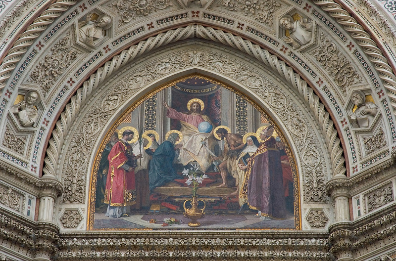 A relgious mural decorates the archway above the door leading into the Duomo in Florence Italy