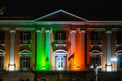 Builds in Naples Italy at night displaying the colors of the Italian flag in lights