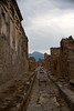 Ancient road inside the ruins of Pompeii with Mount Vesuvius in the background.