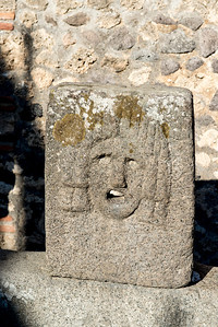 A simple stone sculpture at a water well.