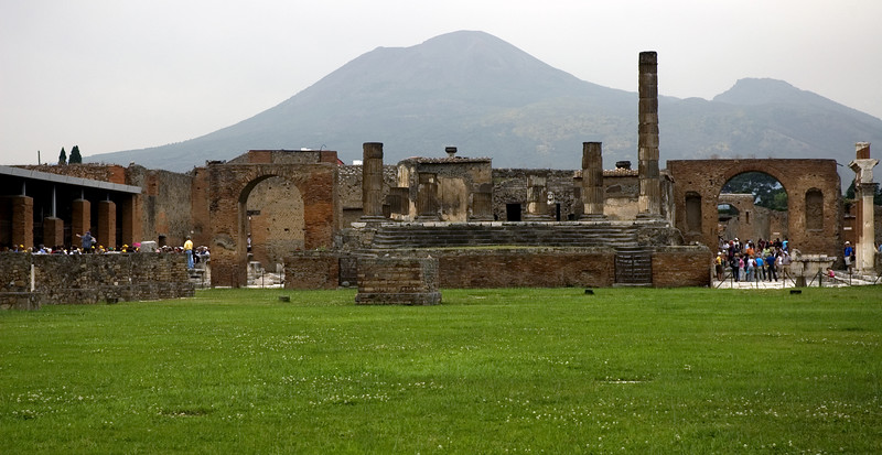 The is the Square or common market place in the ruins of Pompeii with the volcano in the background