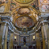 "Main nave and altar (pano). High altar (neo-classical pediment) designed by Antonio Sarti. IHS aureole sculpted by Rinaldo Rinaldi. Angels kneeling are by Francesco Benaglia and Filippo Gnaccarini. Vault of the apse fresco ""Glory of the Mystical Lamb"" by Baciccia, AKA Giovanni Battista Gaulli."