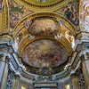 "Main nave and altar. High altar (neo-classical pediment) designed by Antonio Sarti. IHS aureole sculpted by Rinaldo Rinaldi. Angels kneeling are by Francesco Benaglia and Filippo Gnaccarini. Vault of the apse fresco ""Glory of the Mystical Lamb"" by Baciccia, AKA Giovanni Battista Gaulli."