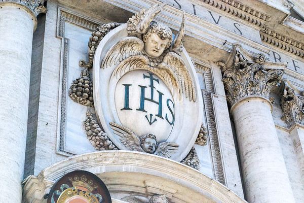 Façade of Church of the Most Holy Name of Jesus at the Argentina, AKA Chiesa del Gesu, AKA Church of the Gesù. Christogram IHS is a monogram symbolizing Jesus Christ. From Greek it is an abbreviation of the name IHΣΟΥΣ (Jesus).