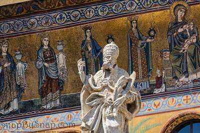 A Christian statue looking out to his followers with an intricate mosaic background