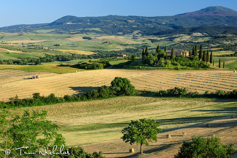 Tuscan farmhouse in the late afternoon - tractor busy baling