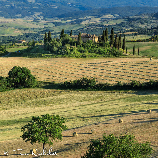 Tuscan farmhouse in the late afternoon - farmer contemplating the baling