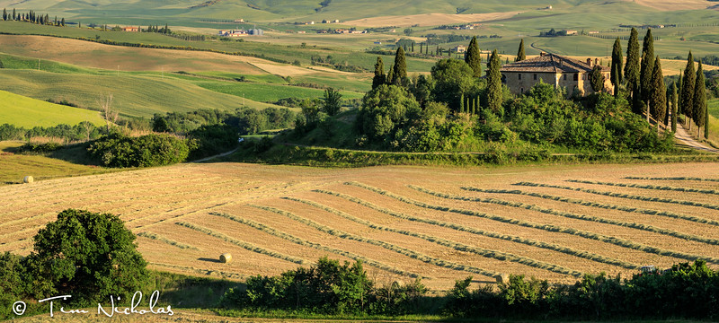 Tuscan farmhouse in the late afternoon - baling in progress