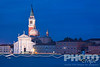 View of church of San Giorgio Maggiore at twilight, with multiple multicoloured wavy lines from motion blurs of boat lights, and water of Canale della Giudecca, lights illuminated along quayside, autumn in Venice, Northern Italy