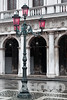 Desaturated image: highly decorated stone balustrade and loggia of Libreria Sansoviana, close up view, traditional ornate wrought iron lampstand with red glass, white markings of Piazzetta under water at Aqua Alta, Venice, Northern Italy