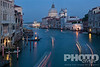 Aerial view of Grand Canal, looking towards church of Santa Maria della Salute, multicoloured lines from motion blur of boat lights at twilight, looking beyond to San Marco Basin, Venice, Northern Italy