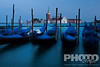 View of San Marco basin, looking past moored gondolas with motion blur in foreground, to San Giorgio Maggiore church and nearby harbour, dusk with lighthouse shining,  autumn  in Venice, Northern Italy