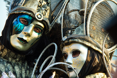 A pair of costumed revelers of the Carnival of Venice in a silver, and blue costume.