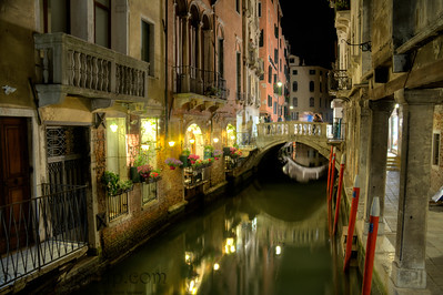 Night time image of a canal in Venice, Italy with lite balconies and a bridge.