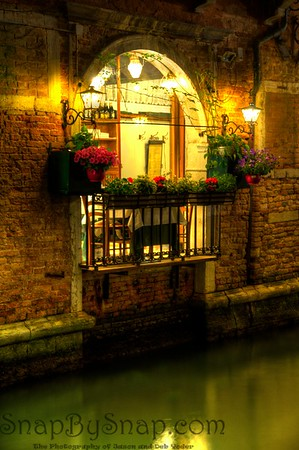 Evening view of a balcony overlooking a canal in Venice, Italy with lights and flowers.