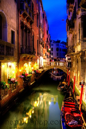 Evening view of a gondola docked in a canal in Venice in the evening.