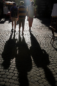 Three pedestrians are trailed by their shadows on a Roman street.