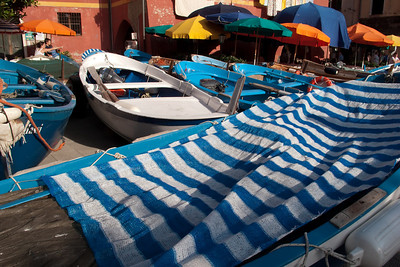 Fishing Boats in the Plaza, Vernazza, Ciinque Terre            Although Vernaza's harbor appears to be spacious and safe, storms frequently whip waves over the breakwater.  Thus customers of sidewalk cafes in the plaza often find fishing boats at their elbows.