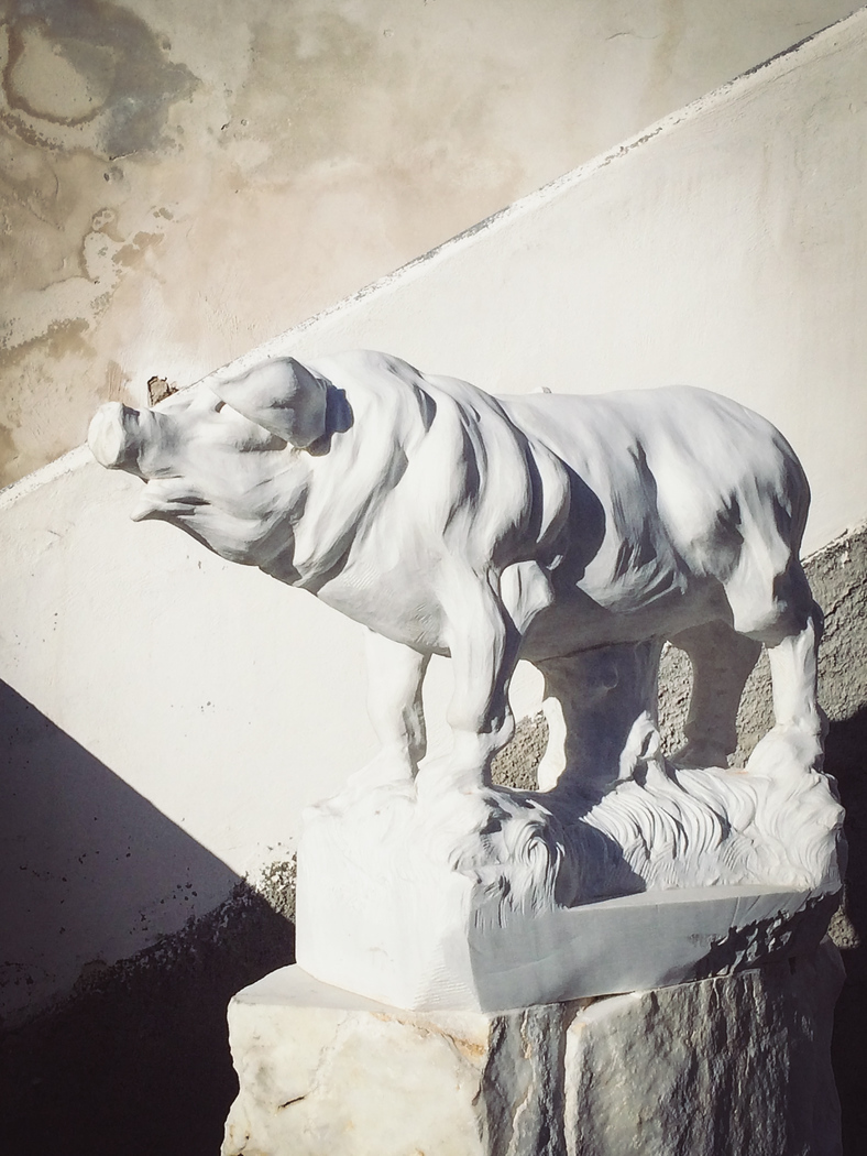 A Marble statue of a pig greets you in the square.