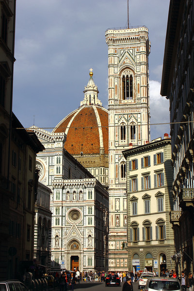 Duomo church, Florence.  From Wikipedia:  The Basilica di Santa Maria del Fiore (English: Basilica of Saint Mary of the Flower) is the main church of Florence, Italy. The Duomo, as it is ordinarily called, was begun in 1296 in the Gothic style to the design of Arnolfo di Cambio and completed structurally in 1436 with the dome engineered by Filippo Brunelleschi. The exterior of the basilica is faced with polychrome marble panels in various shades of green and pink bordered by white.  The basilica is one of Italy's largest churches, and until development of new structural materials in the modern era, the dome was the largest in the world. It remains the largest brick dome ever constructed.